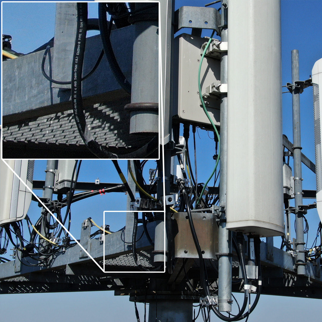 Close-up view of top of cell tower with zoomed inset showing wire markings